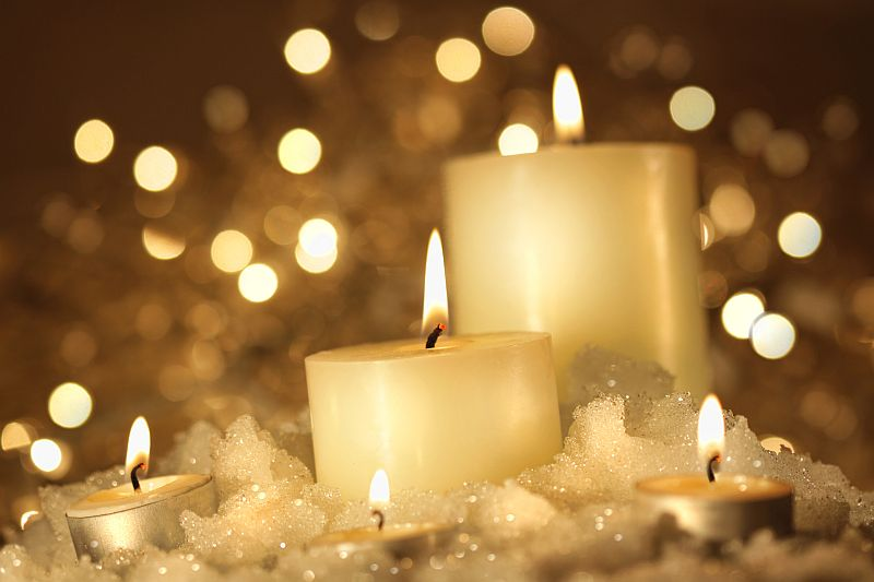 Brightly lit candles in wet snow against sparkly background ...